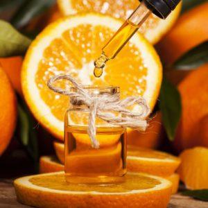 Orangenöl mit aufgeschnittener Orange zur Gewinnung von Organge süß bio (Orangenöl)